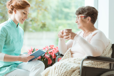 caregiver reading book to her old woman patient