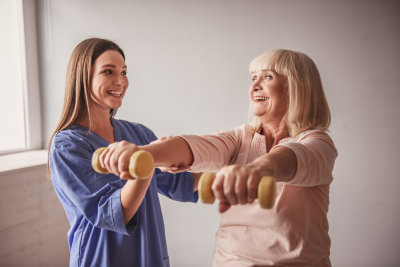female caregiver assisting her patient while doing exercise
