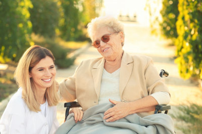 senior woman in wheelchair and her nurse from home care outdoors