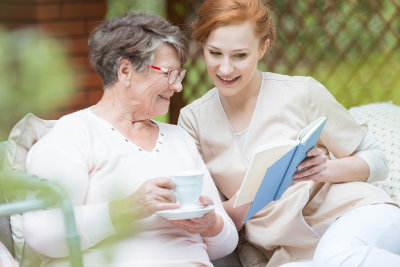 caregiver and her old patient reading book
