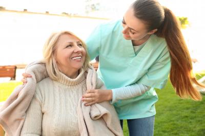 senior woman and female caregiver in park