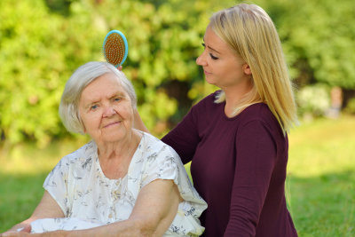 senior woman with her caregiver in park.
